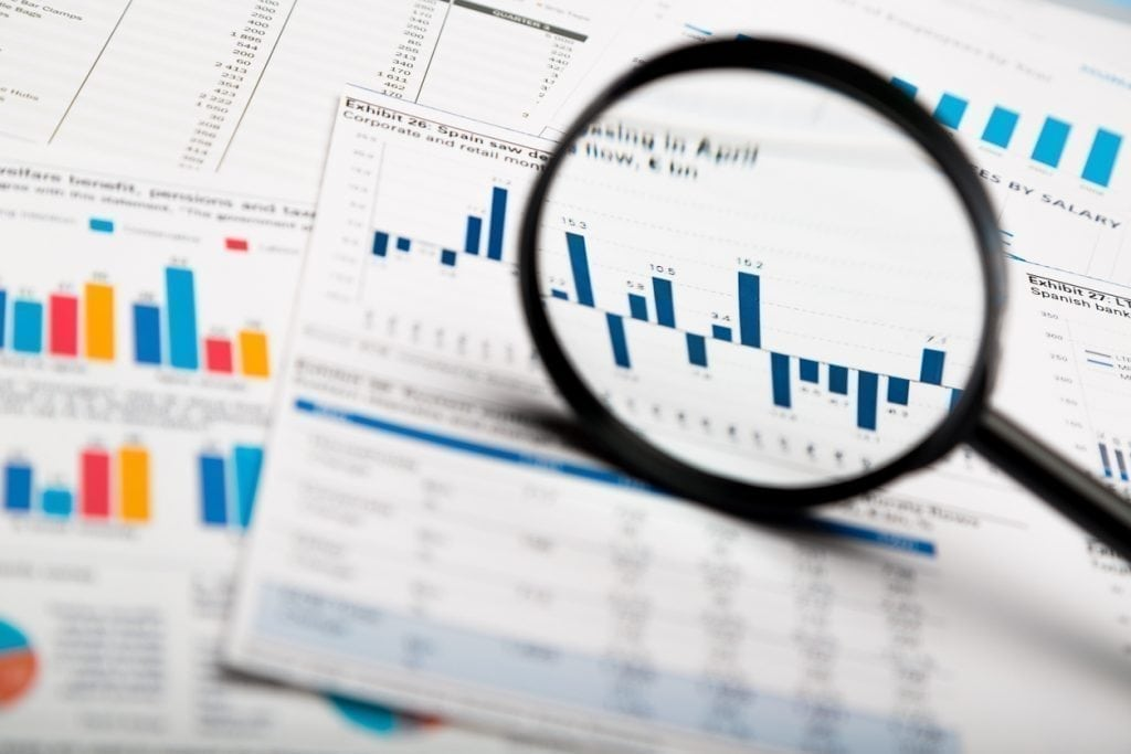 Magnifying glass on business charts